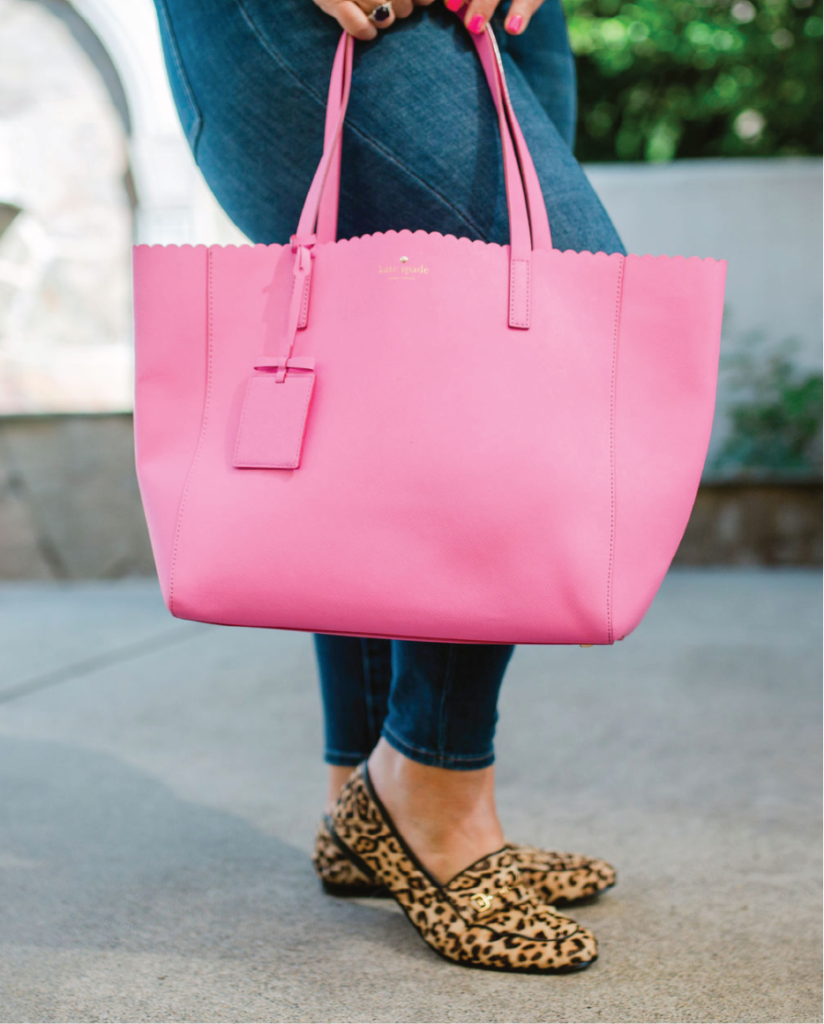 legs wearing jeans with a pink bag