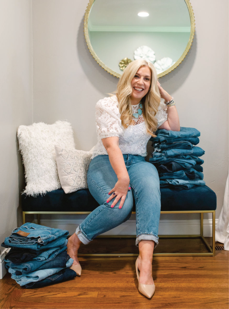 Dawn posing with a stack of jeans
